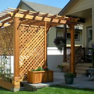 "The Traditional Wooden Garden Pergola (Options: 10' L x 12' W, California Redwood, No Electrical Wiring Trim, Open Roof with Slats at 18"", Rafters at 18"", Widthwise Roof Support Timbers, 4-Post Anchor Kit for Stone, No Ceiling Fan Base, 3 Privacy Panels, No Curtain Rods, 9' Post Height, Transparent Premium Sealant). Photo Courtesy of Bill and Sandy Gibson of Coeur d'Alene, Idaho."