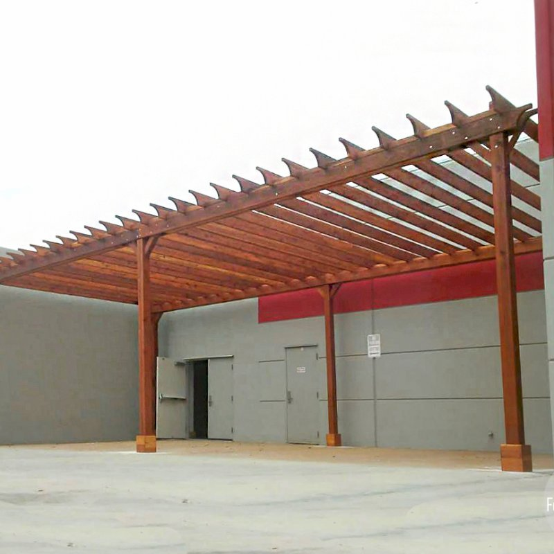 "The Traditional Wooden Garden Pergola (Options: 42' L x 18' W, California Redwood, No Electrical Wiring Trim, Open Roof with Rafters at 18"", Lengthwise Roof Support Timbers, 6-Post Anchor Kit for Concrete, No Ceiling Fan Base, No Privacy Panels, No Curtain Rods, 12' Post Height, Transparent Premium Sealant). This order was customized to not have the standard 2x2 slats above and perpendicular to the main 2x6 rafters. Instead, we added blocking between the 2x6 slats as can be seen above the main support timber headers. Photo Courtesy of J. Porter of Moreno Valley, CA."