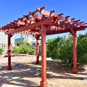 "The Traditional Wooden Garden Pergola (Options: 16' L x 12' W, California Redwood, No Electrical Wiring Trim, Open Roof with Slats at 18"", Rafters at 18"", 4-Post Anchor Kit for Gale-Wind, No Ceiling Fan Base, No Privacy Panels, No Curtain Rods, 9' Post Height, Cherry Stain Premium Sealant). Photo Courtesy of N. Miller of Yuma, Arizona."