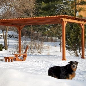 "The Traditional Wooden Garden Pergola (Options: 20' L x 14' W, Mature Redwood, No Electrical Wiring Trim, Slats at 6"" and Rafters at 18"", Lengthwise Roof Support Timbers, 4-Post Anchor Kit for Stone, No Ceiling Fan Base, No Privacy Panels, No Curtain Rods, 9' Post Height, Transparent Premium Sealant). Photo Courtesy of Mary Louise and Gerry Neugent of Des Moines, IA."
