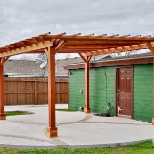 "The Traditional Wooden Garden Pergola (Options: 16' L x 16' W, California Redwood, No Electrical Wiring Trim, Open Roof with Slats at 18"", Rafters at 18"", 4-Post Anchor Kit for Concrete, No Ceiling Fan Base, No Privacy Panels, No Curtain Rods, Two-9' Posts & Two-10' Posts, Transparent Premium Sealant). Customer Requested Slight Slant to the Roof. Photo Courtesy of G. Genoway of Portland, Texas."