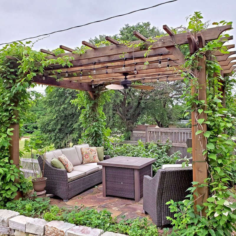 "The Traditional Wooden Garden Pergola (Options: 14' L x 12' W, Mature Redwood, No Electrical Wiring Trim, Open Roof with Slats at 18"", Rafters at 18"", Lengthwise Roof Support Timbers, 4-Post Anchor Kit for Concrete, No Ceiling Fan Base, No Privacy Panels, No Curtain Rods, 9' Post Height, Transparent Premium Sealant). Photo Courtesy of D. Vickery of St. Paul, Minnesota."