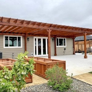 """The Traditional Wooden Garden Pergola (Options: 42' L x 16'-3 1/2"""" W, Old-Growth Redwood by Custom Request, No Electrical Wiring Trim, Open Roof with Slats at 6"""", Rafters at 18"""", 8-Post Anchor Kit for Concrete, No Ceiling Fan Base, No Privacy Panels, No Post Decorative Trims, No Curtain Rod, 10' Post Height, Transparent Premium Sealant). Photo Courtesy of D. Menzel of Santa Rosa, CA."""