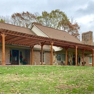 """The Traditional Wooden Garden Pergola (Options: 22' L x 14.5' W & 42' L x 8' W [Connected], Mature Redwood, No Electrical Wiring Trim, Open Roof with Slats at 18"""", Rafters at 18"""", Lengthwise Roof Support Timbers, 9-Post Anchor Kit for Stone, No Ceiling Fan Base, No Privacy Panels, No Curtain Rods, 9.5' Post Height, Transparent Premium Sealant). Photo Courtesy of K. Feliciani of Greensburg, Pennsylvania."""