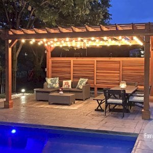 "The Traditional Wooden Garden Pergola (Options: 18' L x 12' W, California Redwood, 1 Electrical Wiring Trim, Open Roof with Slats at 12"", Rafters at 18"", Lengthwise Roof Support Timbers, 4-Post Anchor Kit for Concrete, No Ceiling Fan Base, 1 Louver Privacy Panel Half Height Without Wall, 1 Curtain Rods, 9' Post Height, Transparent Premium Sealant). Photo Courtesy of Sasha Antskaitis of Louisville, Kentucky."