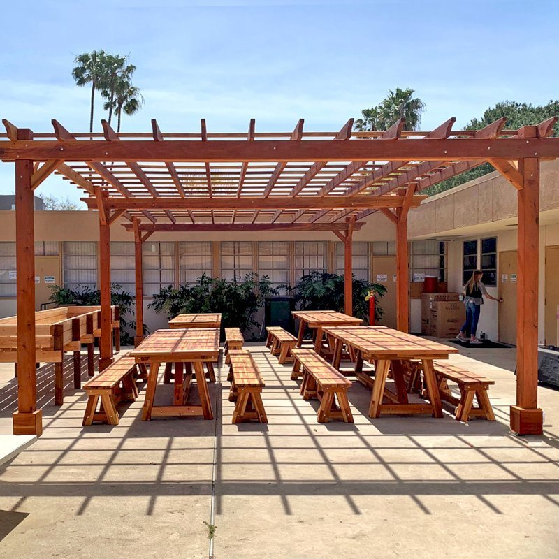 "The Traditional Wooden Garden Pergola (Options: 30' L x 18' W, California Redwood, Electrical Wiring Trim for 2 Posts, Open Roof with Slats at 18"", Rafters at 18"", 6-Post Anchor Kit for Concrete, No Ceiling Fan Base, No Privacy Panels, No Curtain Rods, 10' Post Height, Transparent Premium Sealant). Photo also shows 4 Classic Redwood Patio Tables. Photo Courtesy of T. Sirvent of Costa Mesa, CA."