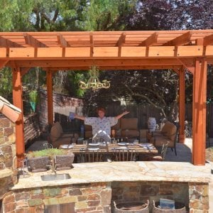 "Garden Pergola Attached to a 18' x 18' Backyard Pavilion (Options: 14' L x 9' W, Mature Redwood, Electrical Wiring Trim for 1 Post, Open Roof with Slats at 18"", Rafters at 18"", Lengthwise Roof Support Timbers, 6 Post Anchor Kit for Gale-Wind, 2 Ceiling Fan Base, No Privacy Panels, No Curtain Rods, 10' Post Height, Transparent Premium Sealant). Photo Courtesy of J. Angwin of Morgan Hill, CA."