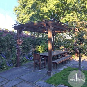"The Traditional Wooden Garden Pergola built in 2012 and photographed in 2016 showing how  California Redwood's finish ages if not retreated, (Options: 18' L x 11' W, Mature Redwood, No Electrical Wiring Trim, Open Roof with Slats at 18"", Rafters at 18"", 4-Post Anchor Kit for Concrete, 9' Post Height, Transparent Premium Sealant). Photo Also Shows a San Francisco Patio Table Set. Courtesy of C. Moseley of Seattle, Washington."