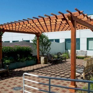 "The Traditional Wooden Garden Pergola (Options: 18' L x 14' W, California Redwood, No Electrical Wiring Trim, Open Roof with Slats at 12"", Rafters at 18"", Widthwise Roof Support Timbers, 4-Post Anchor Kit For Stone, No Ceiling Fan Base, No Privacy Panels, No Curtain Rods, 9' Post Height, Transparent Premium Sealant). Photo Courtesy of Dartmouth Hitchcock Medical Center, Lebanon."