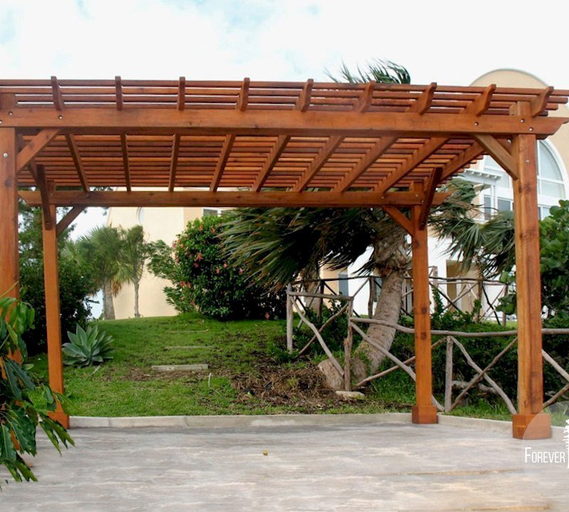 "The Traditional Wooden Garden Pergola (Options: 16' L x 10' W, Mature Redwood, No Electrical Wiring Trim, Open Roof with Slats at 6"" Rafters at 18"", Lengthwise Roof Support Timbers, 4-Post Anchor Kit for Stone, No Ceiling Fan Base, No Privacy Panels, No Curtain Rods, 9' Post Height, Transparent Premium Sealant)."