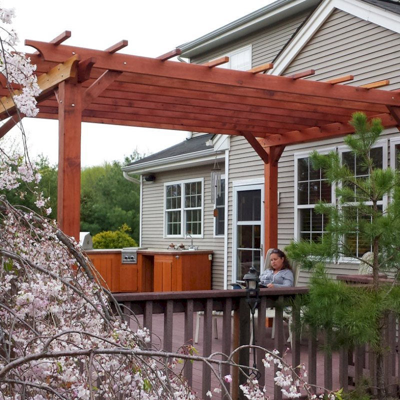 "The Traditional Wooden Garden Pergola (Options: 15' L x 12' W, California Redwood, No Electrical Wiring Trim, Open Roof with Slats at 18"", Rafters at 18"", Widthwise Roof Support Timbers, 4- Post Anchor Kit for Wood, No ceiling Fan Base, No Privacy Panels, No Curtain Rods, 9' Post Height, Transparent Premium Sealant). Photo Courtesy of Ian Clarke of Allentown, NJ."