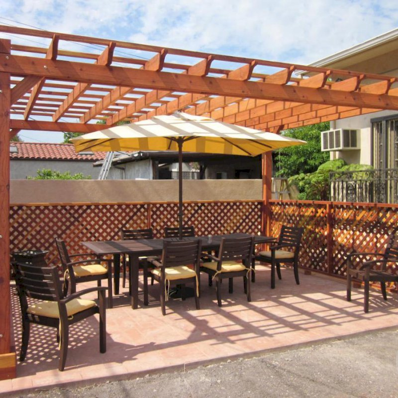 "The Traditional Wooden Garden Pergola (Options: 18' x 14', California Redwood, No Electrical Wiring Trim, Open Roof with Slats at 18"", Rafters at 18"", Lengthwise Roof Support Timbers, 4-Post Anchor Kit for Stone, No Ceiling Fan Base, 3 Privacy Panels, No Curtain Rods, 9' Post Height, Transparent Premium Sealant). Photo Courtesy of Mike W. of Los Angeles, CA."
