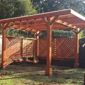 Custom Garden Pergola (Options: 18' x 15', California Redwood, No Electrical Wiring Trim, Widthwise Roof Supports TImbers, 4-Post Anchor Kit for Stone, 2 Privacy Panels, No Curtain Rods, Roof with a Slope, Transparent Sealant) with 2 Rory's Swing Seats, Added by Custom Request. Customer Added Lexan Panels. Photo Courtesy of Tina Phi of Palo Alto, CA.
