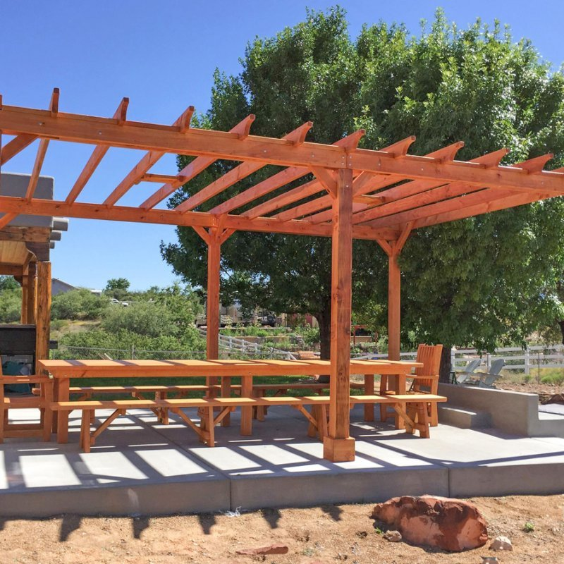 "The Traditional Wooden Garden Pergola (Options: 22' L x 16' W, Douglas-fir, Electrical Wiring Trim for 1 Post, Open Roof with Rafters at 18"", No Slats by Custom Request, Lengthwise Roof Support Timbers, 6-Post Anchor Kit for Concrete, with 2 Ceiling Fan Bases, No Privacy Panels, No Curtain Rods, 9.5' Post Height, Transparent Premium Sealant). Photo Also Shows a San Francisco Table Set. Photo Courtesy of Chris D. of Cornville AZ."