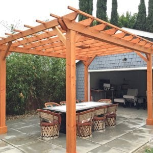 "The Traditional Wooden Garden Pergola (Options: 15' L x 12' W, Douglas-fir, Electrical Wiring Trim for 1 Post, Open Roof with Slats at 18"", Rafters at 18"", Lengthwise Roof Support Timbers, 6-Post Anchor Kit for Concrete, 1 Ceiling Fan Base, No Privacy Panels, No Curtain Rods, Custom 45 Degree End Cuts for Rafters and Support Timbers, 9' Post Height, Transparent Premium Sealant). Photo Courtesy of L. Martling of Los Angeles, CA."