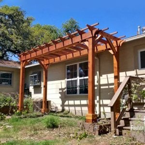 "The Traditional Wooden Garden Pergola (Options: 6' L x 16' W, California Redwood, No Electrical Wiring Trim, Open Roof with Slats at 18"", Rafters at 18"", 4-Post Anchor Kit, No Ceiling Fan Base, No Privacy Panels, No Curtain Rods, 9' Post Height, Transparent Premium Sealant). Photo Courtesy of L. Manning of Boeme, TX."