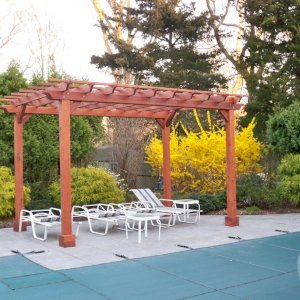 "The Traditional Wooden Garden Pergola (Options: 16' L x 10' W, Mature Redwood, No Electrical Wiring Trim, Open Roof with Slats at 6"", Rafters at 18"", Lengthwise Roof Support Timbers, 4-Post Anchor Kit for Stone, No Ceiling Fan Base, No Privacy Panels, No Curtain Rods, 9' Post Height, Transparent Premium Sealant)."