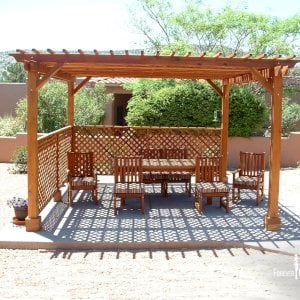 "The Traditional Wooden Garden Pergola (Options: 15' x 15', California Redwood, No Electrical Wiring Trim, Lattice Panel Roof, 4-post Anchor Kit for Stone, No Ceiling Fan Base, 2 Privacy Panels, No Curtain Rods, 9' Post Height, Transparent Premium Sealant). Under the Pergola, a 7' San Francisco Patio Table Set with 42"" W Tabletop, 4 Ruth Chairs and 2 Ruth Armchairs. Photo Courtesy of Mr. Joseph Dlugosz of Sedona, AZ."