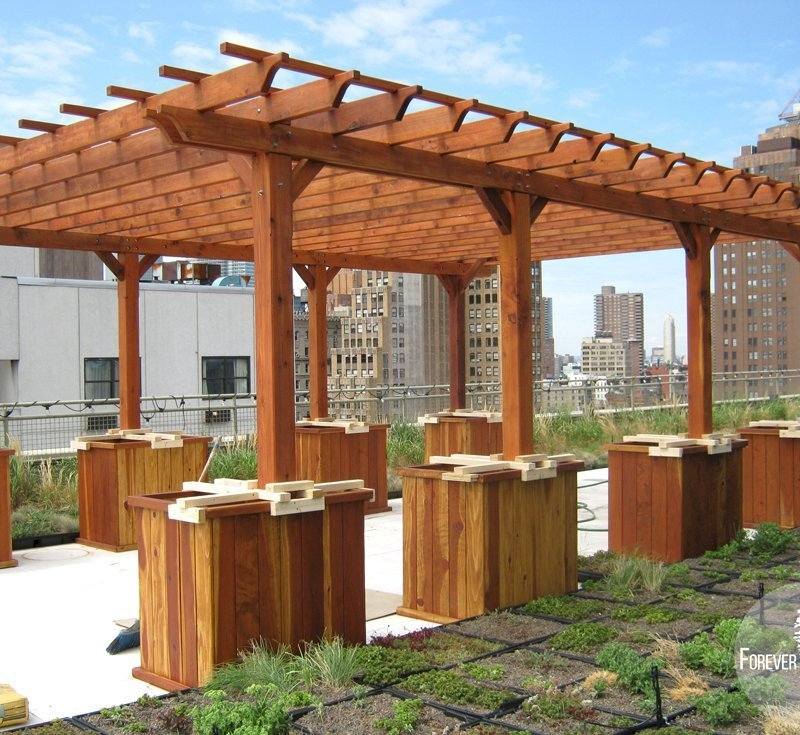 "Typical Roof Top Installation: The Traditional Wooden Garden Pergola (Options: 26' L x 18' W, Mature Redwood, No Electrical Wiring Trim, Rafters at 18"" and Slats at 18"", Lengthwise Roof Support Timbers, 6-Post Anchor Kit for Stone, No Ceiling Fan Base, No Privacy Panels, No Curtain Rods, 9' Post Height, Transparent Premium Sealant). Custom Request: 2 Extra Post. No leak roof installation using planters with concrete. NYC skyline in background."
