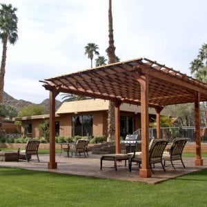 "The Traditional Wooden Garden Pergola (Options: 26' L x 14' W, Mature Redwood, No Electrical Wiring Trim, Open Roof with Slats at 12"", Rafters at 18"", Lengthwise Roof Support Timbers, 6-Post Anchor Kit for Stone, No Ceiling Fan Base, No Privacy Panels, No Curtain Rods, 9' Post Height, Transparent Premium Sealant). Shade Cloth Added by Customer After Installation. Photo Courtesy of Val Kay of Indian Wells, CA."