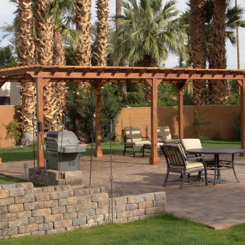 "The Traditional Wooden Garden Pergola (Options: 26' L x 14' W, California Redwood, No Electrical Wiring Trim, Open Roof with Slats at 12"", Rafters at 18"", Lengthwise Roof Support Timbers, 6-Post Anchor Kit for Stone, No Ceiling Fan Base, No Privacy Panels, No Curtain Rods, 9' Post Height, Transparent Premium Sealant). Photo Courtesy of Val Kay of Indian Wells, CA."