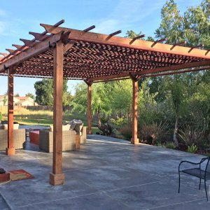 The Traditional Wooden Garden Pergola (Options: 25' L x 18' W, California Redwood, No Electrical Wiring Trim, Lattice Roof, Lengthwise Roof Support Timbers, 6-Post Anchor Kit for Stone, No ceiling Fan Base, No Privacy Panels, 4 Curtains Rods, 9.5' Post Height, Transparent Premium Sealant). Photo Courtesy of Tom Deckowski of Morgan Hill, CA. Note that photo shows 2 yr old finish that is partially faded.