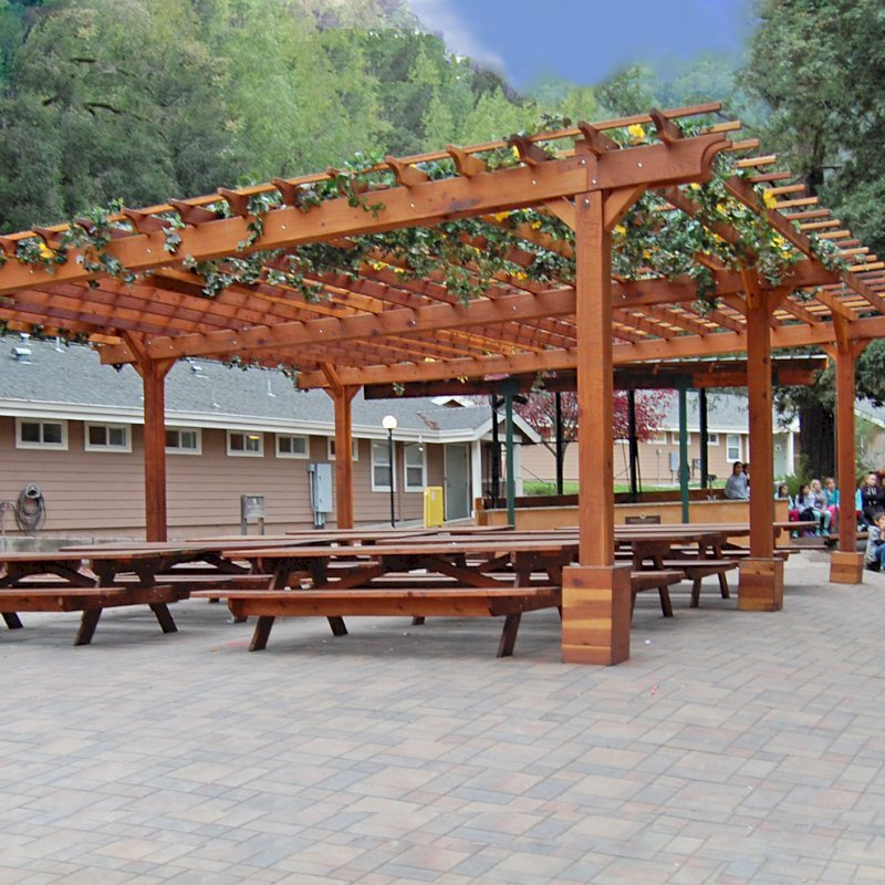 "The Traditional Wooden Garden Pergola (Options: 30' L x 30' W, California Redwood, No Electrical Wiring Trim, Open Roof with Slats at 18"", Rafters at 18"", 6-Post Anchor Kit for Gale-Wind, No Ceiling Fan Base, No Privacy Panels, No Curtain Rods, 10' Post Height, Transparent Premium Sealant). After the tables and pavers were added. Picnic Tables are not Forever Redwood Tables. Photo Courtesy of Via West Campground located at 13851 Stevens Canyon Rd, Cupertino, CA."