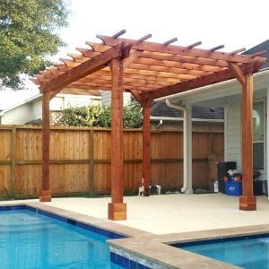 "The Traditional Wooden Garden Pergola (Options: 15' L x 11' W, California Redwood, No Electrical Wiring Trims, Open Roof with Slats at 18"", Rafters at 18"", 4-Post Anchor Kit for Concrete, No Ceiling Fan Base, No Privacy Panels, No Curtain Rods, Transparent Premium Sealant). Photo Courtesy of T. Mullin of Katy, TX."