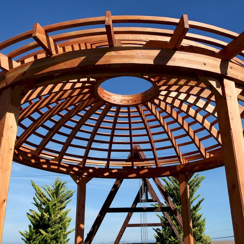 "The Wooden Dome Pergola (Options: 16' Diameter, with Deck in Coffee Stain, Douglas-fir, Open Roof with Slats at 6"", 9' Posts, No Electrical Wiring Trim, 6-Post Anchor Kit for Concrete, Transparent Premium Sealant). Photo Also shows a Round Picnic Table and a Rory's Swing Set in Background."