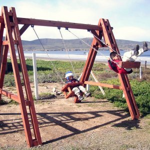 Rory's Grande Playground Swing - Mature Redwood with Toddler/Small Kid's Swing Seat - left (Options: Mature Redwood, Chain & Eye Bolts, Transparent Premium Sealant) and Rory's Swing Seat - right (Options: Mature Redwood, Transparent Premium Sealant).