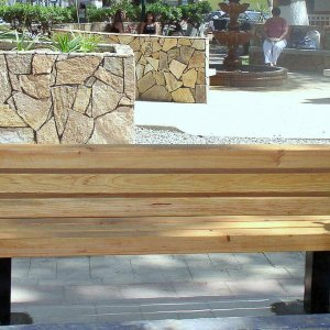 Backside: Veterans Bench (Options: 6 ft, Douglas-fir, Extra Long Legs, No Cushion, No Engraving, Transparent Premium Sealant). Photo was taken just after installation - note wet concrete around bench legs.