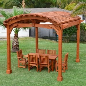 Viking Pergola DIY Kit (Options: 12' L x 14' W, Mature Redwood, Transparent Premium Sealant). Photo Also Shows a Patio Table Set with Ruth Chairs Under the Pergola.