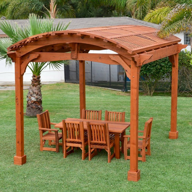 Viking Pergola DIY Kit (Options: 12' L x 14' W, Mature Redwood, No Electrical Wiring Trim Kit, No Curtain Rods, Transparent Premium Sealant). Photo Also Shows a Patio Table Set with Ruth Chairs Under the Pergola.