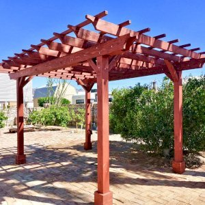 "Garden Pergola (Options: 16' L x 12' W, Redwood, No Electrical Wiring Trim, Open Roof with Slats at 18"", Rafters at 18"", 4-Post Anchor Kit for Gale-Wind, No Ceiling Fan Base, No Privacy Panels, No Curtain Rods, 9' Post Height, Cherry Stain Premium Sealant). Photo Courtesy of N. Miller of Yuma, Arizona."