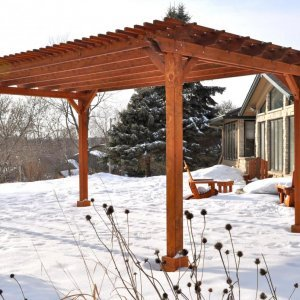"Garden Pergola (Options: 20' L x 14' W, Mature Redwood, No Electrical Wiring Trim, Slats at 6"" and Rafters at 18"", Lengthwise Roof Support Timbers, 4-Post Anchor Kit for Stone, No Ceiling Fan Base, No Privacy Panels, No Curtain Rods, 9' Post Height, Transparent Premium Sealant). Photo Courtesy of Mary Louise and Gerry Neugent of Des Moines, IA."