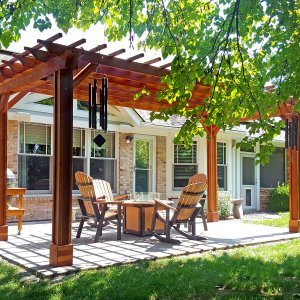 "Garden Pergola (Options: 10' L x 20' W, Redwood, No Electrical Wiring Trim, Open Roof with Slats at 12"", Rafters at 18"", 4-Post Anchor Kit for Concrete, Vertical Post Decorative Trim, No Ceiling Fan Base, No Privacy Panels, No Curtain Rods, Transparent Premium Sealant). Photo Courtesy of J. Karibian of Saint Charles, Missouri."