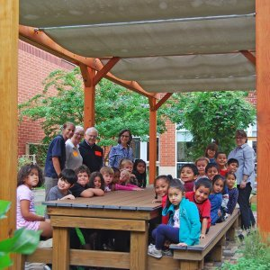 Garden Pergola (Options: 30' L x 12' W, Douglas-fir, Open Roof with Slats at 18, Transparent Premium Sealant). Shade clothe is a wonderful way to increase shade when needed. Shade Clothe shown is a custom detail we can add for you. Photo Courtesy of Frederick Douglass Elementary School of Lessburg, Virginia.