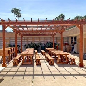"Garden Pergola (Options: 30' L x 18' W, Redwood, Electrical Wiring Trim for 2 Posts, Open Roof with Slats at 18"", Rafters at 18"", 6-Post Anchor Kit for Concrete, No Ceiling Fan Base, No Privacy Panels, No Curtain Rods, 10' Post Height, Transparent Premium Sealant). Photo also shows 4 Classic Redwood Patio Tables. Photo Courtesy of T. Sirvent of Costa Mesa, CA."
