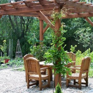 "Garden Pergola (Options: 12' L x 12' W, Old-Growth Redwood, No Electrical Wiring Trim, Open Roof with Slats at 18"", Rafters at 18"", 4 Post Anchor Kit for Stone, No Ceiling Fan Base, No Privacy Panels, No Curtain Rods, 9' Post Height, Transparent Premium Sealant). 4 ft Square Patio Table Set with Luna Armchairs Under the Pergola. Photo Courtesy of Ms. Anne Eccles of Lexington, MA."