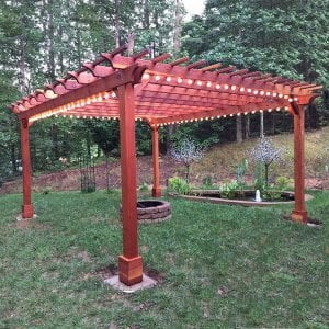 "Garden Pergola (Options: 18' L x 16' W, Redwood, Electrical Wiring Trim for 1 Post, Open Roof with Slats at 12"", Rafters at 18"", Lengthwise Roof Support Timbers, 4-Post Anchor Kit for Gale-Wind, No Ceiling Fan Base, No Privacy Panels, No Curtain Rods, 9' Post Height, Transparent Premium Sealant). Photo Courtesy of A. Miller of Ellijay, Georgia."