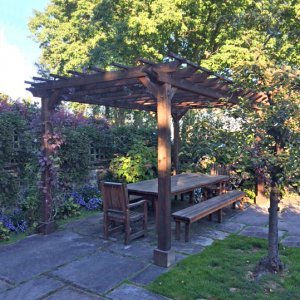"Garden Pergola built in 2012 and photographed in 2016 showing how Redwood's finish ages if not retreated, (Options: 18' L x 11' W, Mature Redwood, No Electrical Wiring Trim, Open Roof with Slats at 18"", Rafters at 18"", 4-Post Anchor Kit for Concrete, 9' Post Height, Transparent Premium Sealant). Photo Also Shows a San Francisco Patio Table Set. Courtesy of C. Moseley of Seattle, Washington."