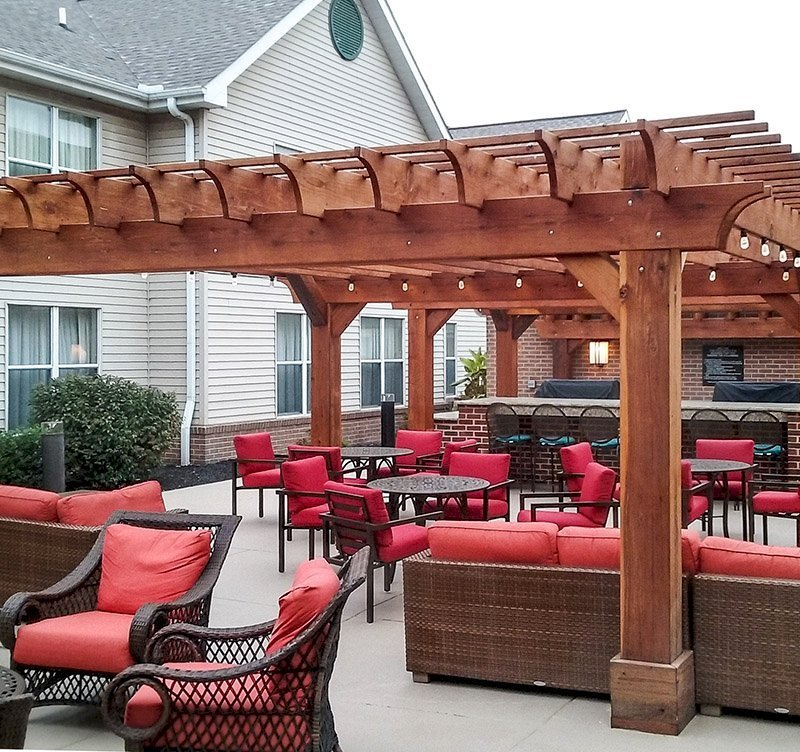 "The Traditional Wooden Garden Pergola (Options: 20' x 20' [2 Smaller Pergolas Shown in the Background], California Redwood, Electrical Wiring Trim for 1 Post, Open Roof with Slats at 12"" and Rafters at 18"", 4-Post Anchor Kit for Concrete, No Ceiling Fan Bases, No Privacy Panels, No Curtain Rods, Transparent Premium Sealant). Thicker Lumber by Custom Request, 2 x 12 Rafters & Supports, 10 x10 Posts. Photo Courtesy of Homewood Suites by Hilton, Mechanicsburg, PA."