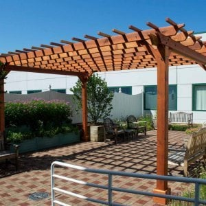 "Garden Pergola (Options: 18' L x 14' W, Redwood, No Electrical Wiring Trim, Open Roof with Slats at 12"", Rafters at 18"", Widthwise Roof Support Timbers, 4-Post Anchor Kit For Stone, No Ceiling Fan Base, No Privacy Panels, No Curtain Rods, 9' Post Height, Transparent Premium Sealant). Photo Courtesy of Dartmouth Hitchcock Medical Center, Lebanon."