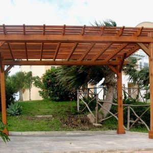 "Garden Pergola (Options: 16' L x 10' W, Mature Redwood, No Electrical Wiring Trim, Open Roof with Slats at 6"" Rafters at 18"", Lengthwise Roof Support Timbers, 4-Post Anchor Kit for Stone, No Ceiling Fan Base, No Privacy Panels, No Curtain Rods, 9' Post Height, Transparent Premium Sealant)."