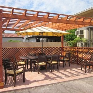 "Garden Pergola (Options: 18' x 14', Redwood, No Electrical Wiring Trim, Open Roof with Slats at 18"", Rafters at 18"", Lengthwise Roof Support Timbers, 4-Post Anchor Kit for Stone, No Ceiling Fan Base, 3 Privacy Panels, No Curtain Rods, 9' Post Height, Transparent Premium Sealant). Photo Courtesy of Mike W. of Los Angeles, CA."