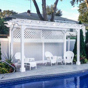 "Garden Pergola (Options: 16' L x 8' W, Douglas-fir, No Electrical Wiring Trim, Open Roof with Slats at 12"", Rafters at 18"", Lengthwise Roof Support Timbers, 4-Post Anchor Kit for Stone, No Ceiling Fan Base, 1 Privacy Panel, No Curtain Rods, 9' Post Height, Off-White Oil-Based Primer). Photo Courtesy of Leo and Genevieve Kirchner of South Amboy, New Jersey."