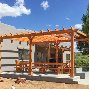 """Garden Pergola (Options: 22' L x 16' W, Douglas-fir, Electrical Wiring Trim for 1 Post, Open Roof with Rafters at 18"""", No Slats by Custom Request, Lengthwise Roof Support Timbers, 6-Post Anchor Kit for Concrete, with 2 Ceiling Fan Bases, No Privacy Panels, No Curtain Rods, 9.5' Post Height, Transparent Premium Sealant). Photo Also Shows a San Francisco Table Set. Photo Courtesy of Chris D. of Cornville AZ."""
