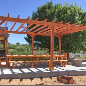 "Garden Pergola (Options: 22' L x 16' W, Douglas-fir, Electrical Wiring Trim for 1 Post, Open Roof with Rafters at 18"", No Slats by Custom Request, Lengthwise Roof Support Timbers, 6-Post Anchor Kit for Concrete, with 2 Ceiling Fan Bases, No Privacy Panels, No Curtain Rods, 9.5' Post Height, Transparent Premium Sealant). Photo Also Shows a San Francisco Table Set. Photo Courtesy of Chris D. of Cornville AZ."