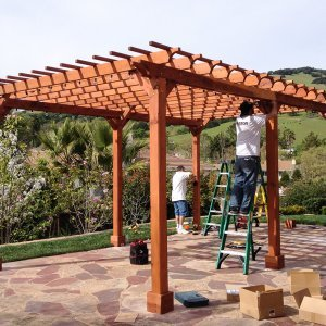 "Garden Pergola (Options: 22' L x 14' W, Mature Redwood, Electrical Wiring Trim for 2 Posts, Open Roof with Slats at 6"", Rafters at 18"", Widthwise Roof Support Timbers, 6-Post Anchor Kit for Concrete, No Ceiling Fan Base, No Privacy Panels, No Curtain Rods, 9.5' Post Height, Transparent Premium Sealant). Photo Courtesy of Roger Cassidy of Novato, CA."
