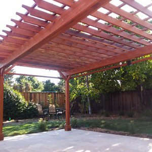 "Garden Pergola (Options: 25' L x 14' W, Redwood, Electrical Wiring Trim for 2 Posts, Open Roof with Slats at 18"", with 2' Overhang by Custom Request, Rafters at 12"", 4-Post Anchor Kit for Gale-Wind, No Ceiling Fan Base, No Privacy Panels, Curtain Rods on 2 Sides, 9.5' Post Height, Transparent Premium Sealant). Photo Courtesy of J. Lewis of Mountain View, CA."